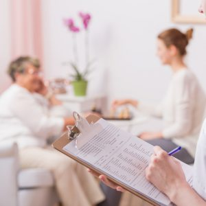 Nurse making notes to medical results with elder woman at the background